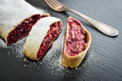 Cherry strudel with almond. And powdered sugar on black slate background Royalty Free Stock Image