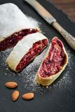 Cherry strudel with almond. And powdered sugar on black slate background Stock Images