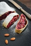 Cherry strudel with almond. And powdered sugar on black slate background Stock Image