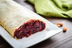Cherry strudel with almond. And powdered sugar on wooden background Stock Photo