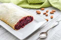Cherry strudel with almond. And powdered sugar on wooden background Stock Photos