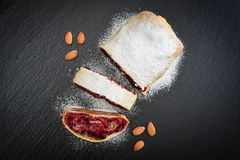 Cherry strudel with almond. And powdered sugar on black slate background, top view Stock Photography