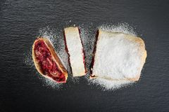 Cherry strudel with almond. And powdered sugar on black slate background, top view Royalty Free Stock Image