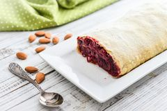 Cherry strudel with almond. And powdered sugar on wooden background Royalty Free Stock Photos