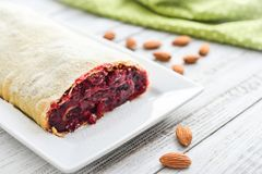 Cherry strudel with almond. And powdered sugar on wooden background Royalty Free Stock Image