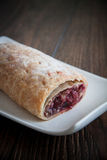 Cherry strudel with almonds. Sweet cherry strudel of puff pastry; two slices on plate royalty free stock images