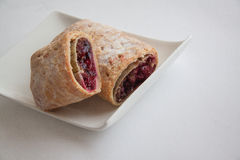 Cherry strudel with almonds. Sweet cherry strudel of puff pastry; two slices on plate stock photo
