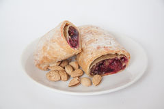 Cherry strudel with almonds. Sweet cherry strudel of puff pastry; two slices on plate royalty free stock image