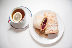 Cherry strudel with almonds. Sweet cherry strudel of puff pastry; two slices on plate royalty free stock photos