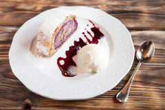 Cherry strudel cake served with ice cream on wooden table at res Stock Photo