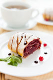 Cherry strudel on white plate and a cup of tea Royalty Free Stock Images