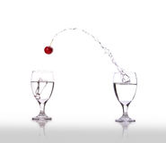Cherry Suction. A cherry being sucked from one glass to another Royalty Free Stock Photos