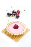 Cherry tart and cherries in the background. Cherry tart on wooden coaster, cherries in the background Stock Photo