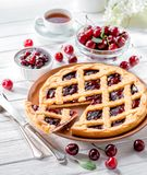 Cherry tart on white wooden background served with fresh berries stock image