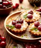 Cherry Tarts con las natillas y el caramelo, postre delicioso de la vainilla en una tabla de madera fotos de archivo