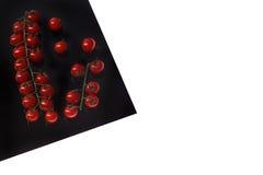 Cherry Tomat sullo strato nero isolato su bianco immagine stock