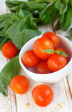 Cherry tomato. In a white bowl with basil and nuts Stock Photography