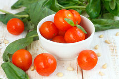 Cherry tomato. In a white bowl with basil and nuts Stock Images