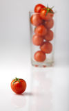 Cherry tomato. Against a glass with tomatoes Stock Image