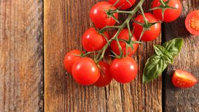 Cherry tomato and basil. On wood Stock Images