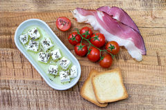 Cherry tomato, cheese in olive oil with basil, toasted bead and prosciutto on wooden background Stock Image