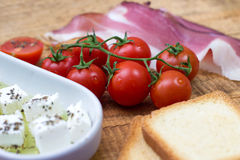 Cherry tomato, cheese in olive oil with basil, toasted bead and prosciutto on wooden background Stock Images