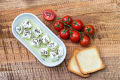 Cherry tomato, cheese in olive oil with basil, toasted bead on wooden background Royalty Free Stock Image