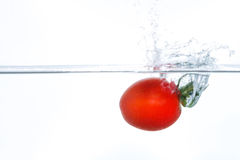 Cherry tomato falling into water with a splash Stock Photos