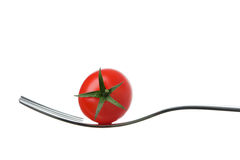 Cherry tomato on a fork against white Royalty Free Stock Images