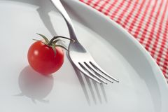 Cherry tomato and fork on plate Royalty Free Stock Photo