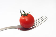 Cherry tomato on the fork and white background Stock Image
