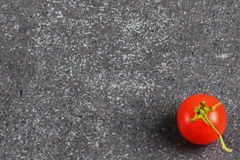 Cherry tomato on a grey abstract stone background. Space for text. Stock Photo