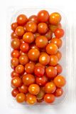 Cherry tomato in plastic container package, studio shoot on whit. Cherry tomato in plastic cointainer packed and ready for market. Package of 500g, studio shoot Stock Image