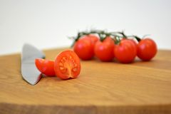Cherry tomato. A sliced cherry tomato on a kitchen table Royalty Free Stock Photos