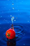 Cherry tomato in water1. A small cherry tomato falling in blue water with  interesting splash Stock Photos