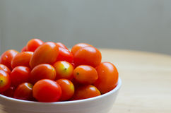 Cherry Tomato In White Bowl. Red cherry tomatos in white ceramic bowl on wood table Stock Images
