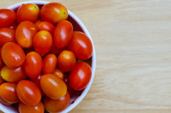 Cherry Tomato In White Bowl. Red cherry tomatos in white ceramic bowl on wood table Royalty Free Stock Images
