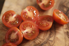 Cherry tomatoea halves on olive cutting board Stock Image