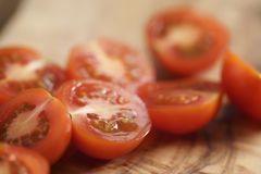 Cherry tomatoea halves on olive cutting board Stock Photos