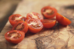 Cherry tomatoea halves on olive cutting board Royalty Free Stock Photography