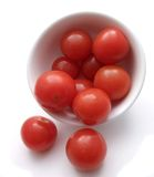 Cherry tomatoes. Cup of cherry tomatoes spilling out on white Stock Photo