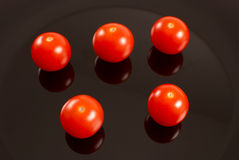 Cherry tomatoes. Freshly picked cherry tomatoes reflecting on a black plate Stock Photos