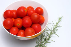 Cherry tomatoes. Bowl of red cherry tomatoes and some rosemary Stock Photos