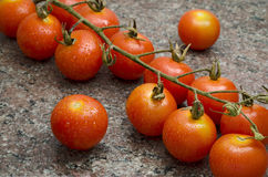 Cherry Tomatoes. Close up of cherry tomatoes on a granite surface Royalty Free Stock Images