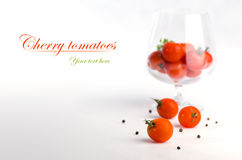 Cherry tomatoes. With black pepper on white background with  in glass royalty free stock image