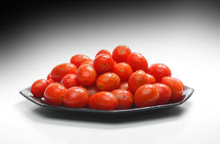 Cherry tomatoes. Lot of cherry tomatoes with drops over a black plate. Look at my gallery for more fresh fruits and vegetables stock images