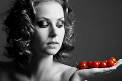 Cherry tomatoes. Beautiful girl in black and white holding bright red tomatoes Royalty Free Stock Images