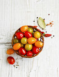 Cherry tomatoes assortment in a basket with spices Royalty Free Stock Photos