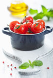 Cherry tomatoes and basil in casserole Stock Image