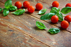 Cherry tomatoes and basil. Fresh leaves of basil placed with cherry tomatoes on wooden background Stock Image